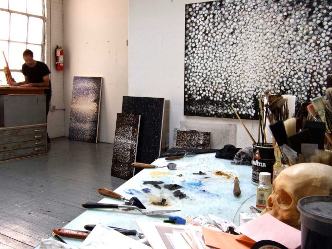 studio view with artist Randall Stoltzfus in the background. Artists palettle table in foreground with skull and paints. A large black and white pixelated painting hangs to the right